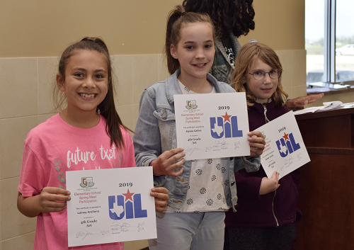 Three girls holding their UIL certificates.