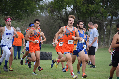 Boy's cross country team takes off across the field.