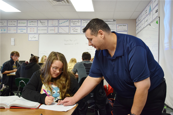 Mr. Becker leans over students to offer help