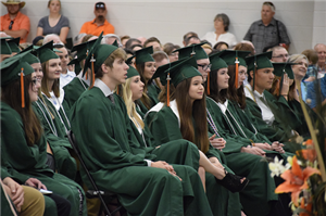 Group of graduates listening to speaker at ceremony.