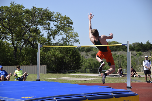 Kelley jumps over the bar in the high jump.