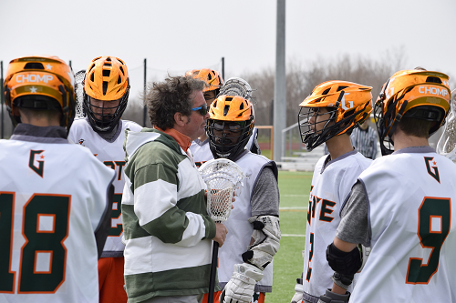 Lacrosse players huddle around coach.