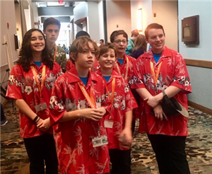 Group photo of boys on robotics team all dressed in red Hawaiian shirts.