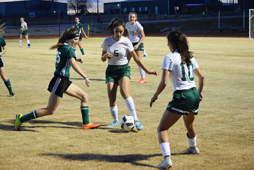 Gator soccer player in middle of opponents