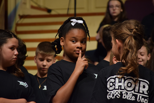 MS choir girl with finger to mouth.