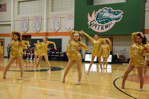 Dancers dressed in gold outfits performing in gym.
