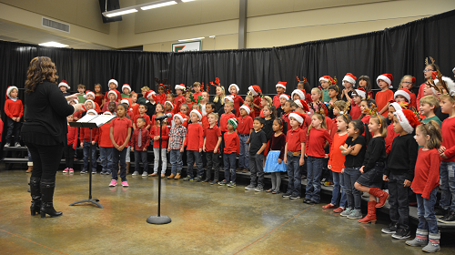 group photo of elementary choir students dressed as Santa.