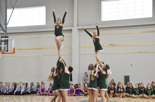 Cheer team doing a pyramid stance at pep rally.