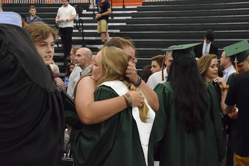 Parent hugging her graduate following ceremony.