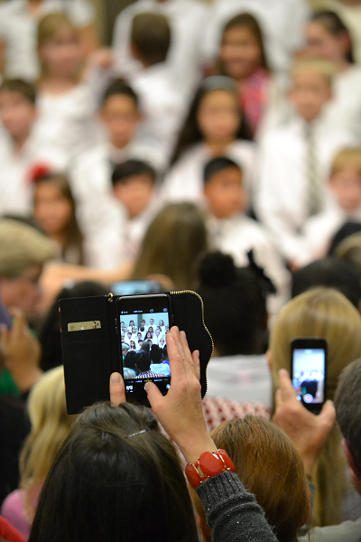 Parents taking photos of choir students.